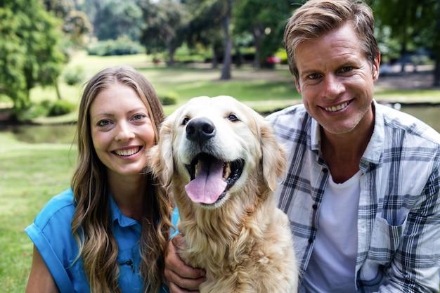 Casal sentado no parque com seu cachorro