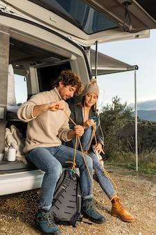 Casal sentado no porta-malas do carro durante uma viagem