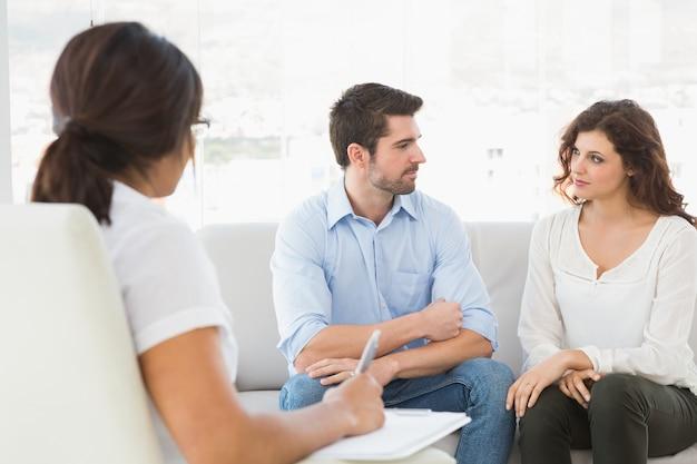 Casal sentado no sofá conversando com seu terapeuta
