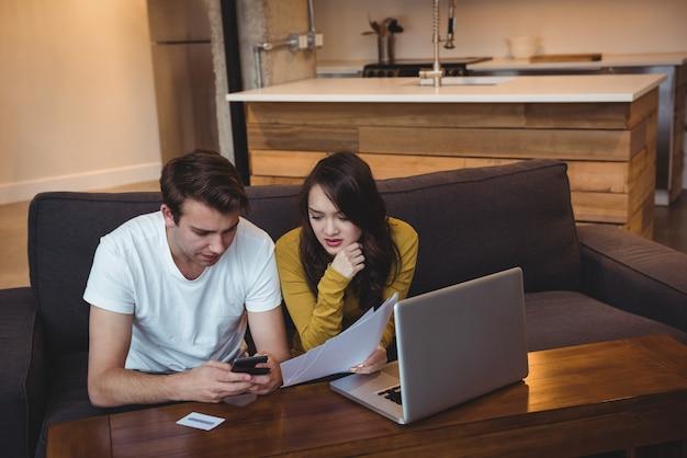Casal sentado no sofá discutindo documentos financeiros na sala de estar