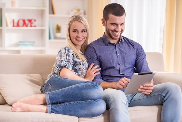 Casal sentado no sofá em casa, usando um tablet.
