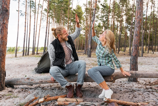 Casal sentado no tronco de uma árvore, mais cinco