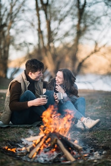 Casal sentado perto da fogueira