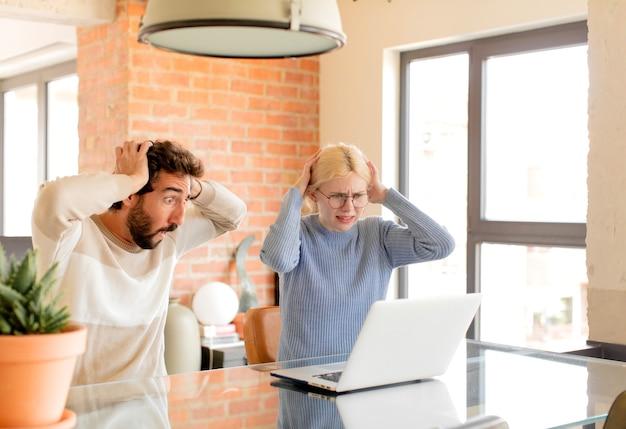 Casal sentindo-se estressado, preocupado, ansioso ou com medo, com as mãos na cabeça, entrando em pânico com o erro