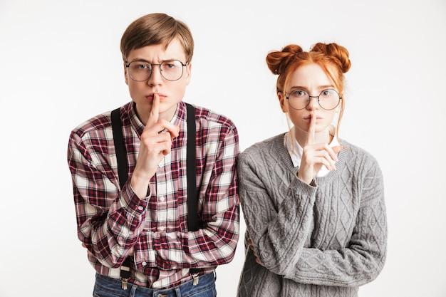 Casal sério de nerds da escola mostrando gesto de silêncio