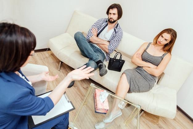 Casal sério e atencioso está sentados juntos no sofá com as mãos cruzadas. eles estão olhando para o terapeuta. médico está olhando e conversando com este casal.