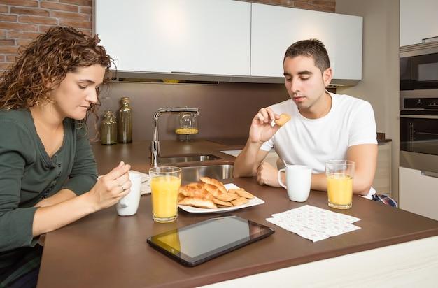Casal sério e entediado tomando café em casa