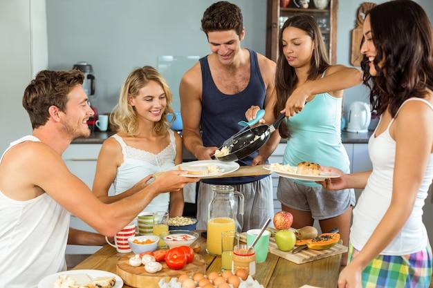 Casal servindo café da manhã para os amigos na mesa