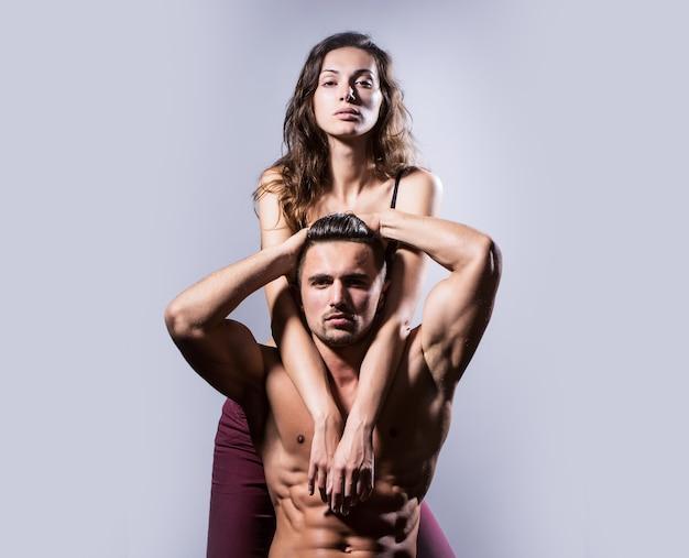 Casal sexy com torso nu musculoso e corpo atlético em estúdio em cinza