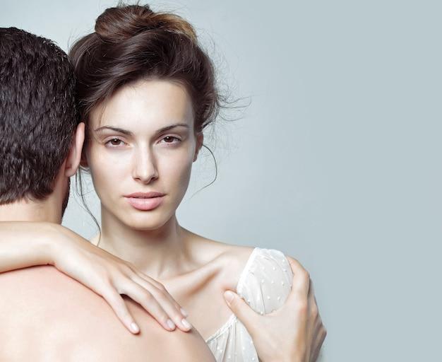 Casal sexy de homem musculoso se abraçando de costas e uma linda mulher ou menina em estúdio em cinza