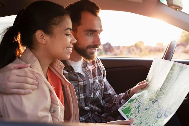 Casal sorridente a verificar o mapa enquanto está sentado no carro