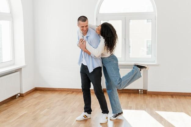 Casal sorridente abraçado em sua nova casa vazia