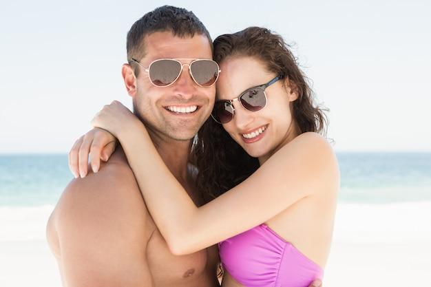 Casal sorridente, abraçando na praia