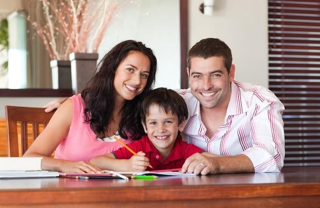 Casal sorridente ajudando seu filho a fazer a lição de casa