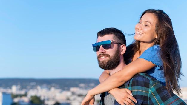 Casal sorridente ao ar livre na cidade com espaço de cópia