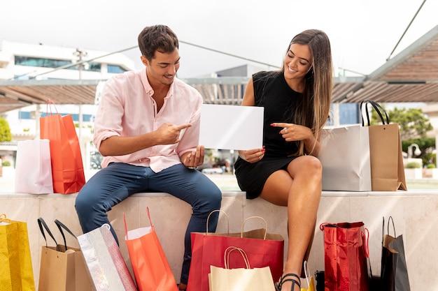 Casal sorridente apontando e segurando o cartão em branco