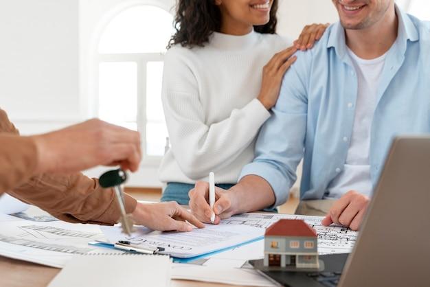 Casal sorridente assinando contrato para nova casa