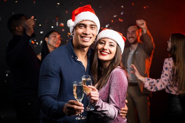 Casal sorridente brindando na festa