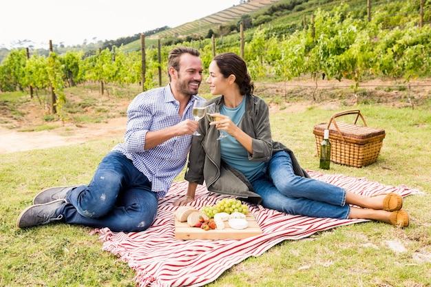 Casal sorridente, brindando o copo de vinho