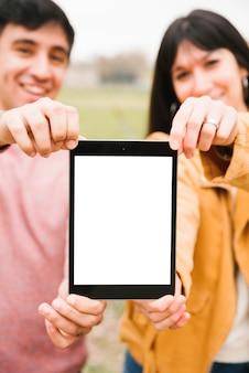 Casal sorridente carregando tablet