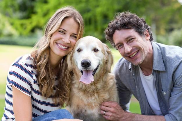 Casal sorridente com cachorro no parque