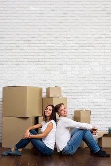 Casal sorridente com caixas e cópia-espaço