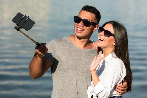 Casal sorridente com óculos de sol tirando uma selfie na praia