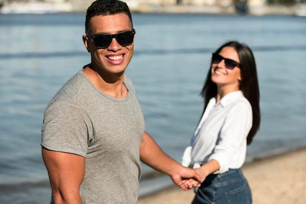 Casal sorridente com óculos escuros de mãos dadas na praia