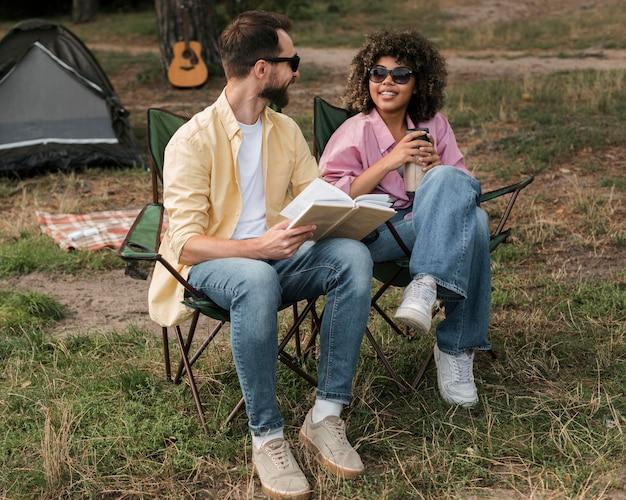 Casal sorridente com óculos escuros lendo e bebendo enquanto acampa ao ar livre