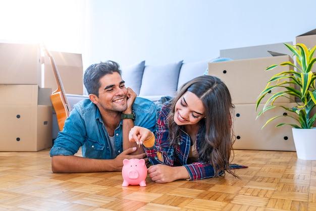 Casal sorridente com piggybank em nova casa