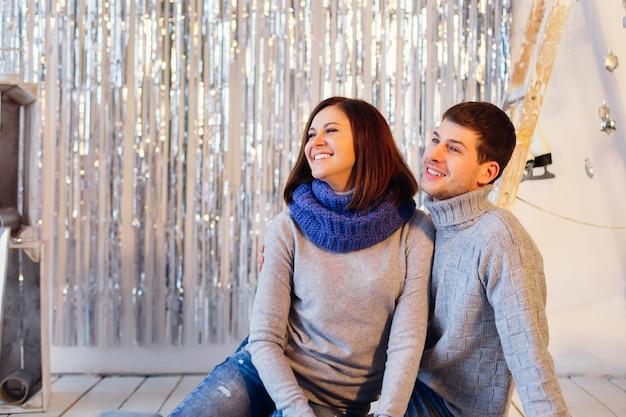 Casal sorridente com roupas de inverno está no lado esquerdo da foto