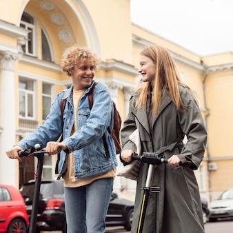Casal sorridente com scooters elétricas ao ar livre