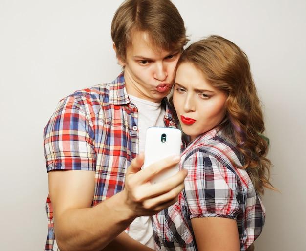 Casal sorridente com smartphone, selfie e diversão.