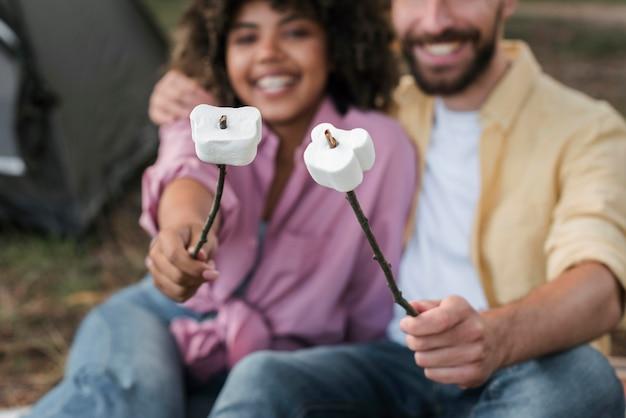 Casal sorridente comendo marshmallows ao acampar
