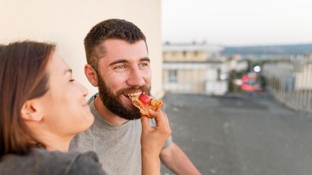 Casal sorridente comendo pizza ao ar livre