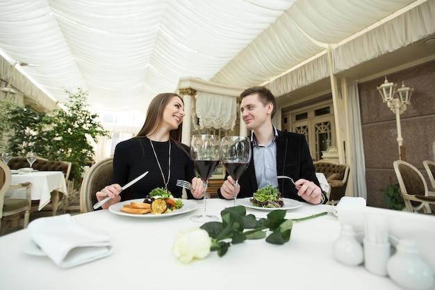 Casal sorridente comendo prato principal no restaurante