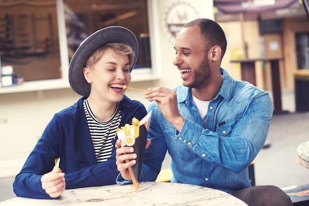 Casal sorridente compartilhando fast food