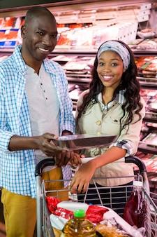Casal sorridente, compras na seção de compras no supermercado