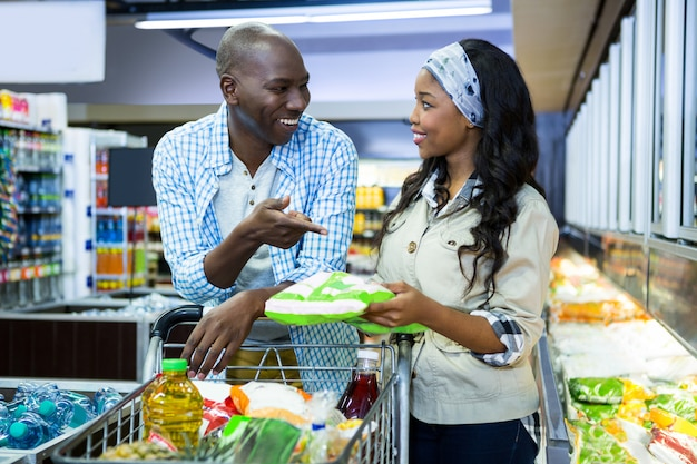 Casal sorridente, compras na seção de compras