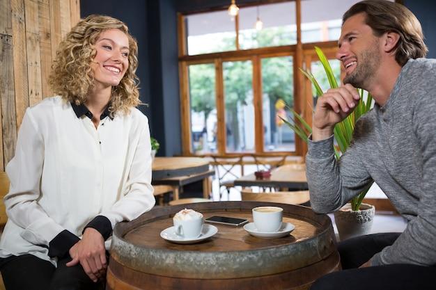 Casal sorridente conversando com xícaras de café na mesa do café