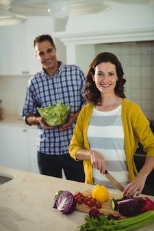 Casal sorridente cortar legumes na cozinha em casa