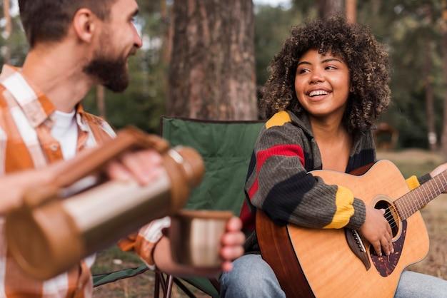 Casal sorridente curtindo acampar ao ar livre com violão e bebida quente