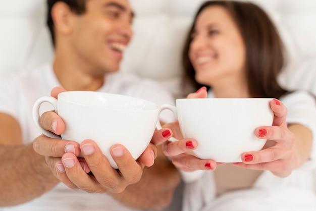 Casal sorridente de close-up com copos de café