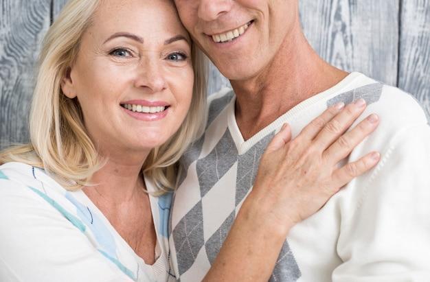 Casal sorridente de close-up com fundo de madeira