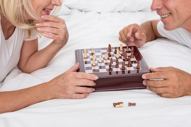 Casal sorridente de close-up jogando xadrez