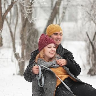 Casal sorridente de close-up, sentado na neve ao ar livre