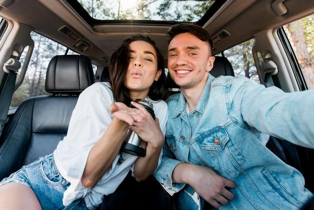 Casal sorridente de frente para tirar uma selfie no carro