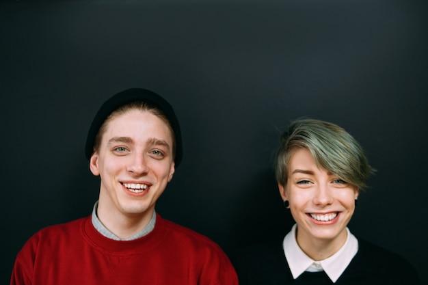 Casal sorridente de hipster. retrato de jovem adolescente e mulher. estilo de vida jovem e estilos de moda. namorada e namorado em fundo escuro