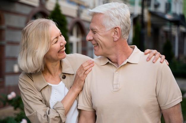 Casal sorridente de idosos caminhando juntos pela cidade