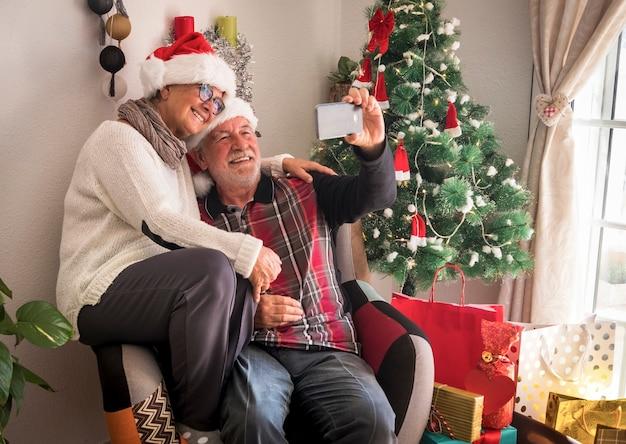 Casal sorridente de idosos com boné de papai noel sentados juntos usando um telefone inteligente para uma selfie